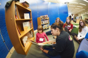 Helen Sharma SSH'17 reads a book from the Favat collection to a young guest.