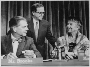 Eleanor Roosevelt is seated at a table on the Meet the Press set. She is smiling at a man standing behind her. Host Ned Brooks is seated next to them.