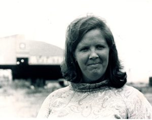 Photo of Mary Ellen Welch, a white woman of Irish descent in black and white. She is smiling with her mouth closed and looking straight on into the camera.