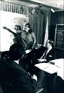 Photo of Mary Ellen Welch, a white woman, pointing to a spot on what looks to be a neighborhood map. She is in a room with two other men seated watching her presentation.