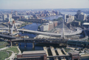Aerial view of Charles River crossing with partially constructed bridge.