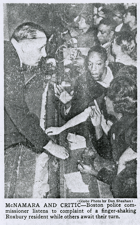 Scanned newspaper photograph of Boston Police Commissioner Edmund McNamara leaning forward and listening to a large group of citizens. The caption reads: McNAMARA AND CRITIC - Boston police commissioner listens to complaint of a finger-shaking Roxbury resident while others await their turn.