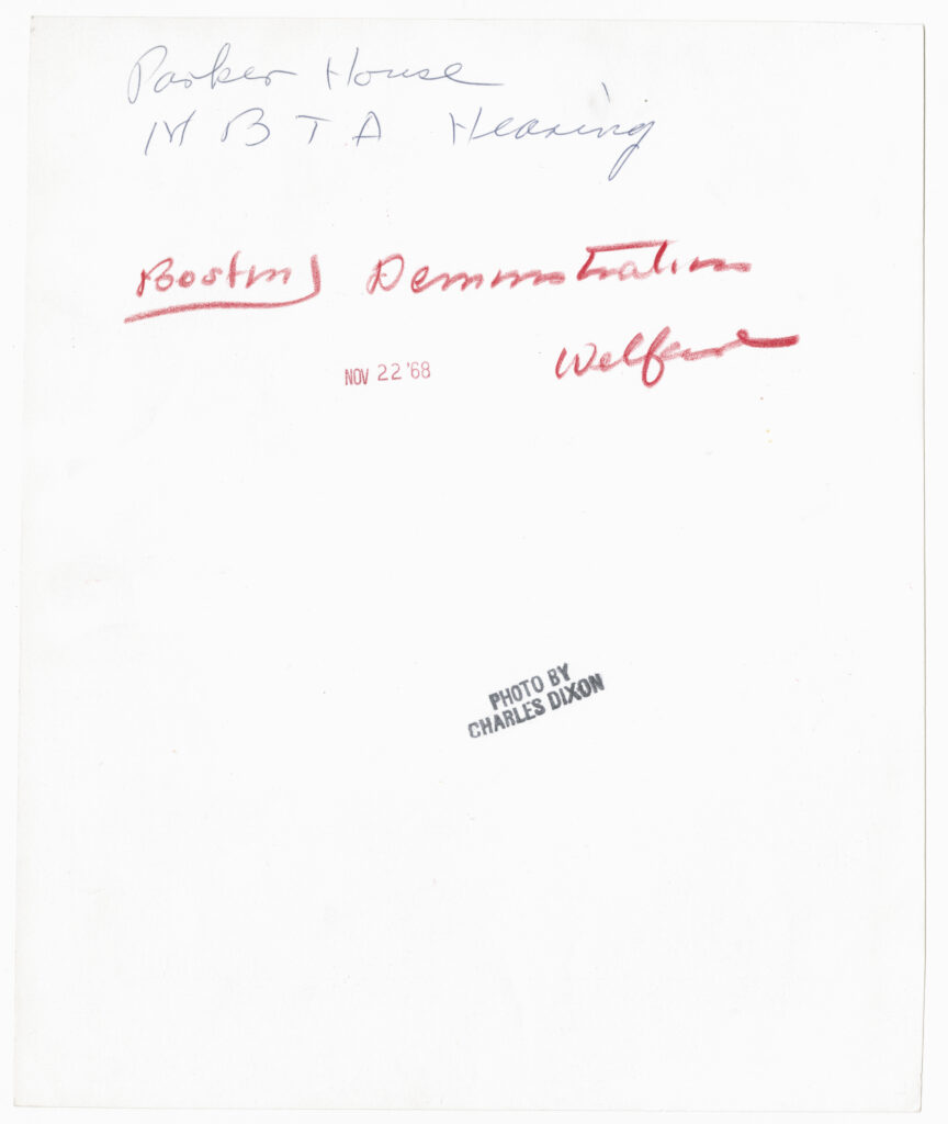 The back of a photograph from the Boston Globe Library Collection, featuring difficult-to-read handwritten descriptions.