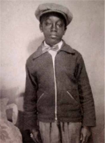 Scanned black-and-white photo of George Stinney, a young boy wearing a dark jacket and hat